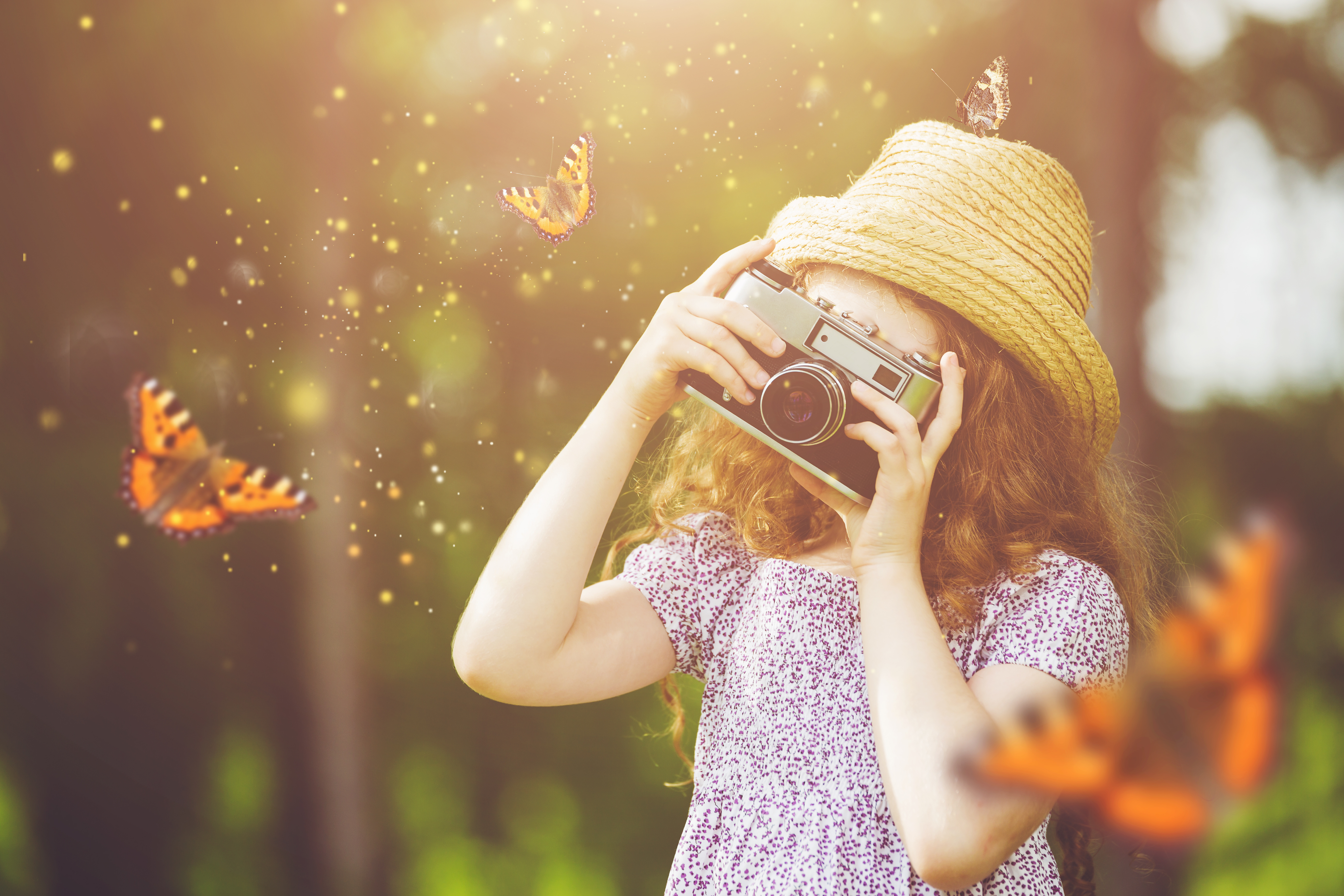 little-girl-photographing-butterfly-in-light-forest